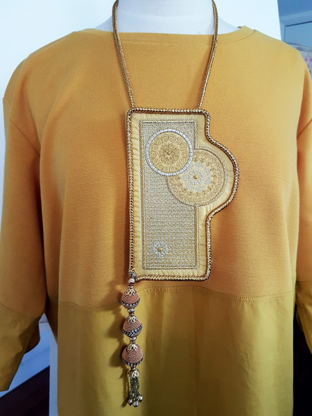 Grand Entrance Machine Embroidery Designs. Artistic modern style necklace in gold which has been embroidered.